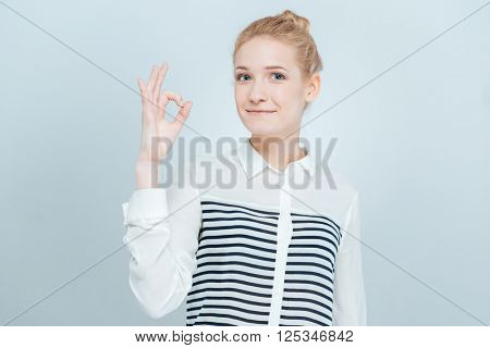 Cute woman showing ok sign with fingers isolated on a white background
