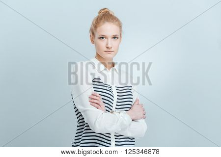 Young woman standing with arms folded isolated on a white background and looking at camera