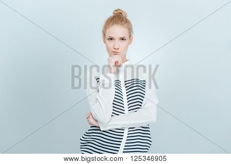 Thoughtful woman looking at camera isolated on a white background