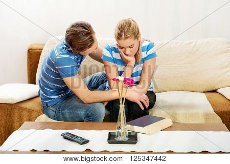 Man comforting his upset partner in living room