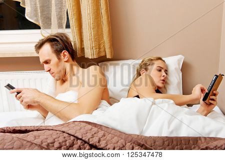 Young happy couple in a bed with mobile phones