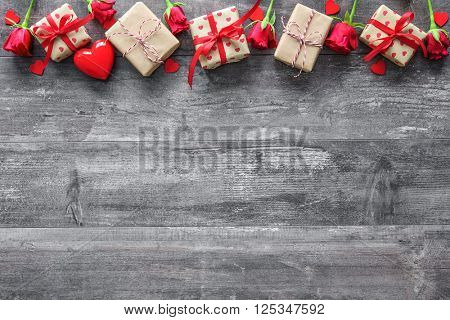 Valentines day vintage background with red roses and gift boxes on wooden board