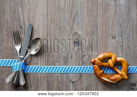 Bavarian cutlery on wooden table with copy space. Oktoberfest beer festival background. Menu for Bavarian specialties