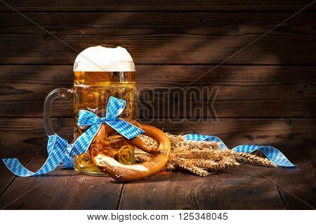 Original bavarian pretzels with beer stein on wooden board. Oktoberfest background