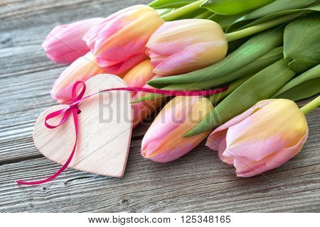 Colorful tulips and heart on wooden background. Valentines day, Mothers day, Birthday, Easter background