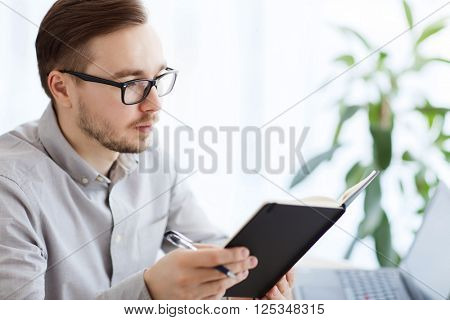business, startup and people concept - businessman or creative male office worker with book or diary and pen at home office
