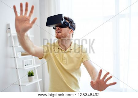 technology, gaming, entertainment and people concept - happy young man with virtual reality headset or 3d glasses playing video game at home