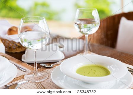food, cooking and eating concept - close up of creamy soup and water glasses on table at restaurant or home