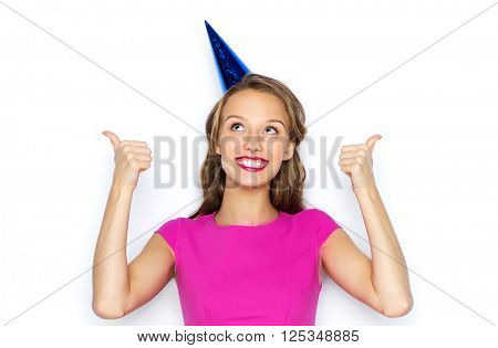 people, holidays and celebration concept - happy young woman or teen girl in pink dress and party cap