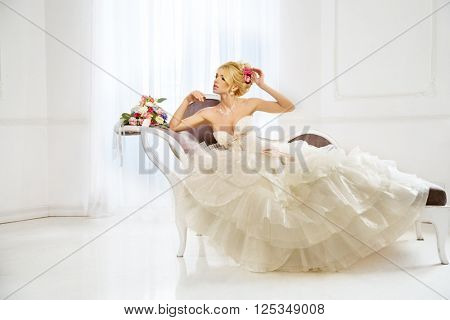 Beautiful fashion model. Sensual bride. Woman with wedding dress, hair and make up. Waiting for groom on background of window. Natural manicure. Beauty spring girl with bouquet of flowers in hands