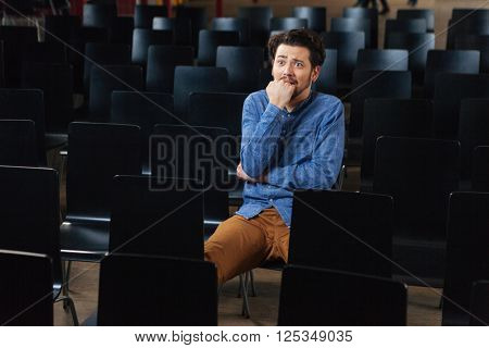 Stressed man in casual cloth sitting in conference hall