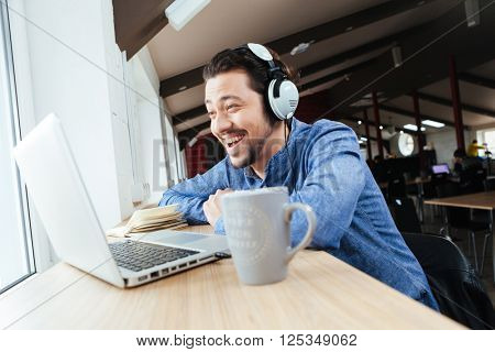 Cheerful man in headset using laptop computer in office