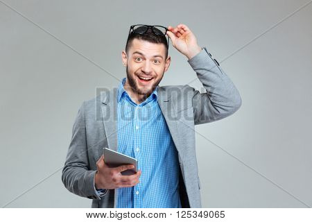 Cheerful businessman holding tablet computer over gray bakground