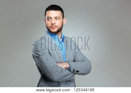 Businessman with arms folded looking away over gray background