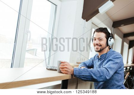 Smiling man sitting at the table with headset and laptop computer and drinking coffee in office