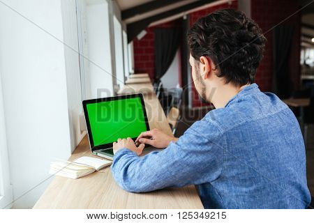 Man using laptop computer with blank screen in office