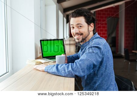 Happy man drinking coffee in office and looking at camera