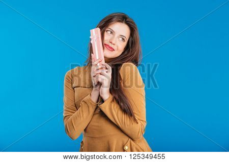 Smiling playful young woman standing and posing with small pink gift box over blue background