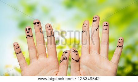 gesture, family, wedding, people and body parts concept - close up of two hands showing fingers with smiley faces over natural green herbal background