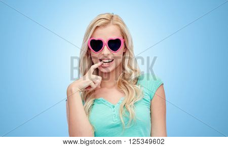 emotions, expressions, summer and people concept - smiling young woman or teenage girl in heart shape sunglasses over blue background