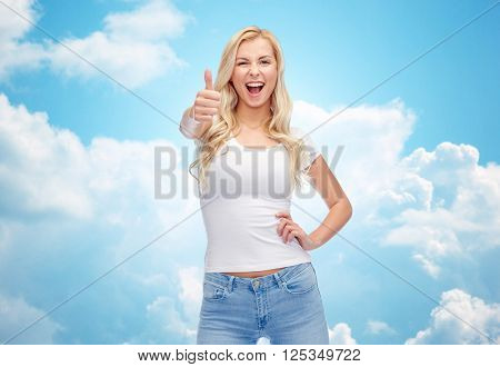emotions, expressions, advertisement and people concept - happy smiling young woman or teenage girl in white t-shirt showing thumbs up over blue sky and clouds background