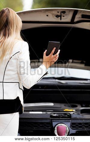 Woman peeks under the open hood