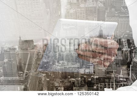 Businessman scrolling on his digital tablet against new york skyline