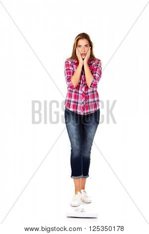 Shocked woman standing on weight scale