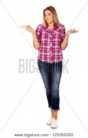 Young woman holding huge cloth spin and gesturing dont know
