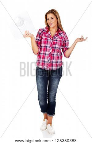 Young woman holding a scale and gesturing dont know