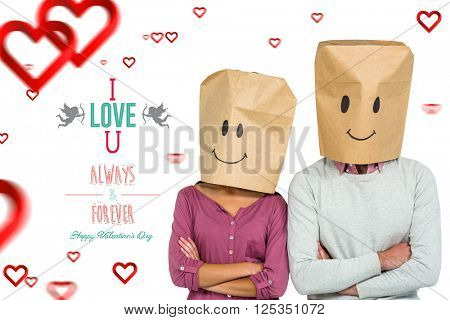 Couple covering their faces with paper bag with arms crossed against cute valentines message