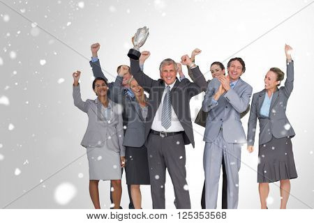 Excited business team cheering at camera with trophy against snow