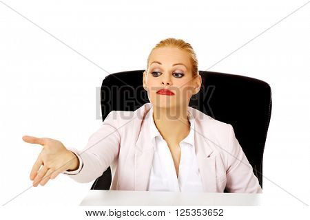 Business woman sitting behing the desk and pointing for the second chair