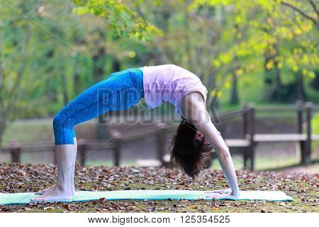 Japanese woman outside doing yoga pose Backbend