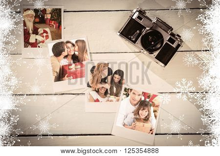 Father and his daughter offering a gift against instant photos on wooden floor