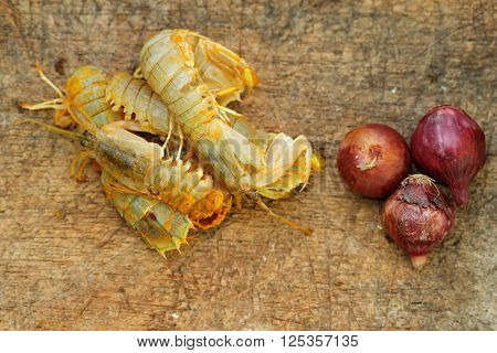 Silver mantis shrimp or known as udang ketak and udang lipan in Malaysia with small onion on old wooden chopping board. Shrimp ready to be cooked after mixed with turmeric and salt.