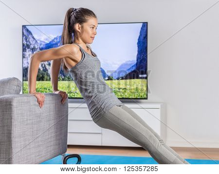 Home fitness woman strength training arms watching online tv dvd workouts doing bodyweight exercises in living room using sofa to do triceps exercise. Exercising Asian girl in her apartment indoors.