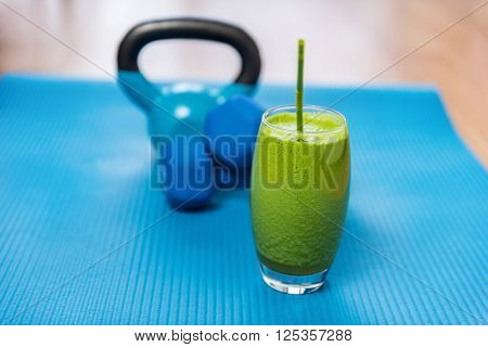 Weight loss healthy eating green vegetable smoothie with free weights kettlebells and exercise mat in gym center. Health and fitness concept. Vegetarian diet and nutrition for strength training.