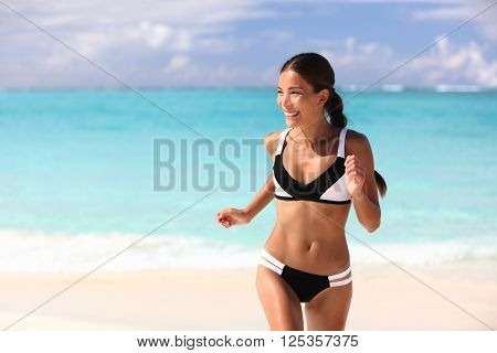 Happy bikini woman having fun on beach holiday on tropical summer travel vacation. Sexy cute Asian girl with slim suntan body running playful sunbathing in sunny Caribbean destination.