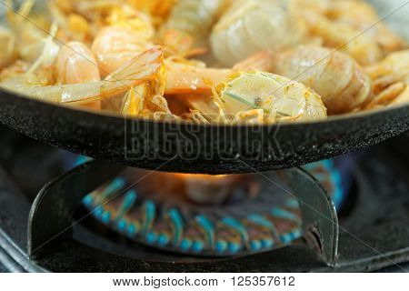 Silver Mantis Shrimp and Prawn cooked in the wok. Upper half picture showing shrimp and prawn inside the wok and below half picture showing the gas stove.In the middle of cooking process.