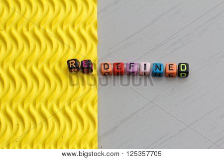 Plastic alphabet block arranged to form word REDEFINED. Two different texture represent the word redefined.