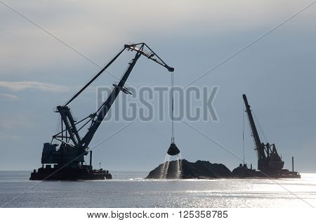 dredger pumping sand onto the coastline to gain new land from the sea