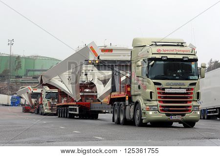 NAANTALI FINLAND - APRIL 9 2016: Two Scania R620 trucks which haul long industrial objects on drop deck trailer as oversize load are parked on a yard. The length of the vehicle is 42 meters.