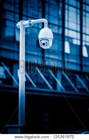 security camera in front of the office building,blue toned image.