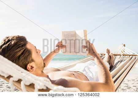 Man reading book in hammock on the beach