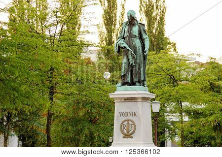 LJUBLJANA SLOVENIA - JULY 9 2009: Statue of Valentin Vodnik on a stone pedestal a Slovene priest journalist and poet at Vodnik square near the Central Market. RF stands for Republique Francaise