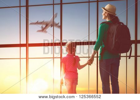 Happy family with child at the airport. Mother and child daughter look out the window at the airplane.