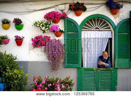 Bari Italy. May 9 2015: man looking out the door of his house with the facade decorated with colorful flower pots