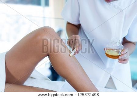 Woman getting her legs waxed at spa