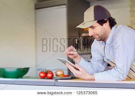 Male entrepeneur in his takeaway food kitchen using his phone